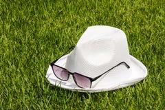 Biali okulary przeciwsłoneczni na zielonej trawie i kapelusz Zdjęcie Royalty Free