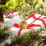 Biali pudełka dekorowali czerwonego faborek Jingle Bell i metal Bożenarodzeniowa wakacyjna dekoracja Zdjęcia Royalty Free