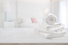 Biali ręczniki na drewnianej powierzchni nad zamazanym sypialni wnętrza tłem Zdjęcie Royalty Free