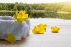 Biali ręczniki z żółtymi kwiatami na drewnianej podłoga na zamazanym jeziora i lasu tle Zdjęcia Royalty Free