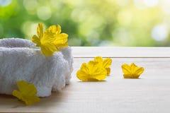 Biali ręczniki z żółtymi kwiatami na drewnianej podłoga na zamazanym zielonym bokeh tle Zdjęcia Stock