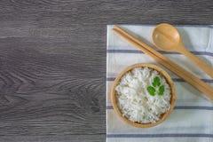 Biali ryż, gotujący biali ryż, gotujący prości ryż w drewnianym pucharze z łyżką i chopsticks, Organicznie ryż na wieśniaku drewn fotografia royalty free