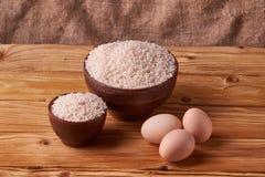Biali ryż w glinianym pucharze na stole i jajkach na drewnianym tle Pojęcie azjaty jedzenie obraz stock