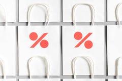 Biali torba na zakupy od przetwarzają papier z procentu znakiem na szarym tle Fotografia Stock