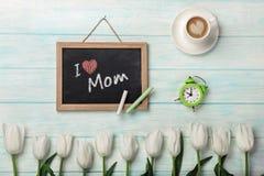 Biali tulipany z kredową deską, filiżanka kawy i budzikiem na błękitnych drewnianych deskach, dzień macierzysty s zdjęcie royalty free