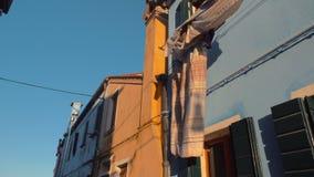 Biancheria da letto che fluttua nel vento su una delle facciate di Burano italiano video d archivio