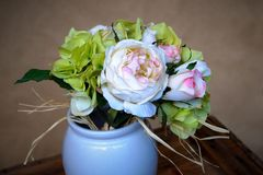 bianco blu della tavola del vaso della peonia dei fiori artificiali e foglie verdi dei petali rosa sulla tavola di legno e sul fo immagine stock libera da diritti