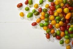 Bianco de sul tavolo di legno del colorati de Pomodorini Imagen de archivo