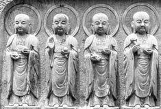 In bianco e nero, fila del primo piano delle statue di pietra di bodhisattva di Jizo nel tempio di Hase-dera Fotografia Stock