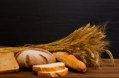 Bianco e pane di segale, una pagnotta, un covone sulla tavola di legno, fondo nero Fotografia Stock