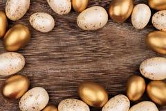 Bianco e struttura dell'uovo di Pasqua dell'oro sopra legno rustico Fotografie Stock Libere da Diritti