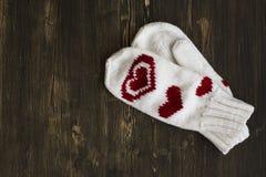 Bianco riscaldi i guanti tricottati sopra fondo di legno Fotografia Stock