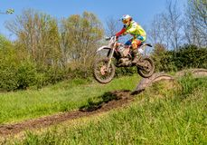 Motocross rider in jumping from the trampoline above the road. Open competitions in motocross in province of Varese. Royalty Free Stock Photos