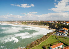 Biarritz between continuous waves and blue sky. Permanent green waves surge in Atlantic coast. The azure sky with a lot of white clouds is over Bay of Biscay stock image