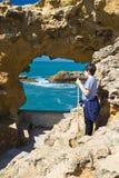 Biarritz, França - 20 de maio de 2017: menino novo que olha através do furo da caverna do mar que admira a vista bonita em Oceano Fotos de Stock