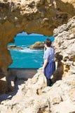 Biarritz, França - 20 de maio de 2017: menino novo que olha através do furo da caverna do mar que admira a vista bonita em Oceano Fotografia de Stock Royalty Free