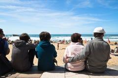 Biarritz, França - 20 de maio de 2017: opinião traseira os povos que olham e que tomam fotos dos surfistas na competição surfando Imagens de Stock