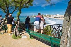 Biarritz, França - 20 de maio de 2017: opinião traseira os povos que olham e que tomam fotos dos surfistas na competição surfando Imagens de Stock Royalty Free