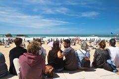 Biarritz, França - 20 de maio de 2017: Sandy Beach completamente dos povos que olham e que tomam fotos do competit surfando dos j Fotos de Stock Royalty Free