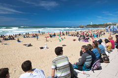 Biarritz, França - 20 de maio de 2017: Sandy Beach completamente dos povos que olham e que tomam fotos do competit surfando dos j Fotografia de Stock Royalty Free