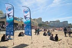 Biarritz, France - 20 mai 2017 : les gens s'asseyant sur la plage sablonneuse et les surfers de observation en concurrence surfan Photos stock