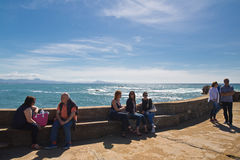 Biarritz, France - May 20, 2017: people sitting down and enjoying spring warm sun on atlantic coastline in basque country in sunny Stock Photo