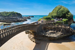 Biarritz, France - May 20, 2017: people walking on footbridge leading to cliff island over sandy beach in touristic destination su Royalty Free Stock Images