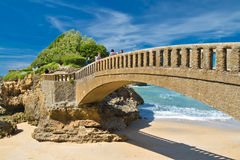 Biarritz, France - May 20, 2017: people walking on stone footbridge in scenic seascape on atlantic coastline in blue sky Royalty Free Stock Photography