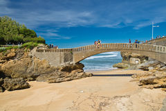Biarritz, France - May 20, 2017: people walking on stone footbridge in scenic seascape on atlantic coastline in blue sky Stock Photo
