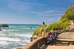 Biarritz, France - May 20, 2017: Young couple admiring beauty of seascape on atlantic coast in springtime with blooming trees in b Stock Photography