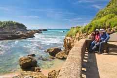 Biarritz, France - May 20, 2017: Young couple admiring beauty of seascape on atlantic coast in springtime with blooming trees in b Stock Photos