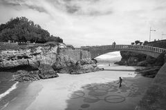 Biarritz, France - October 4, 2017: upper view on man artist creating sand drawing with wooden stick. On sandy beach in scenic seascape of atlantic coastline Royalty Free Stock Images