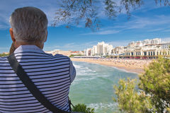 Biarritz, Francia - 20 de mayo de 2017: opinión trasera el hombre mayor que toma las fotos de la playa arenosa escénica en Océano Imagen de archivo
