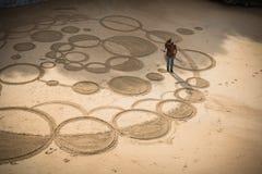 Biarritz, Francia - 4 de octubre de 2017: opinión superior sobre el artista del hombre que crea el dibujo de la arena con el pali Fotografía de archivo