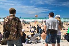 Biarritz, Frankrijk - Mei 20, 2017: achtermening van mensen op overvol zandig strand die en op foto's van surfersisa wereld lette Stock Afbeelding