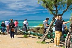 Biarritz, Frankrijk - Mei 20, 2017: achtermening van toeristen die en foto's van mooie toneel Atlantische kust met golf bezienswa Royalty-vrije Stock Fotografie