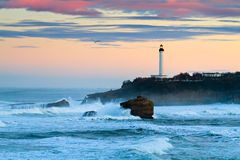Biarritz Lighthouse in the Storm. The iconic lighthouse of Biarritz, under a pinkish morning sky. Big waves hitting the rocks royalty free stock photography