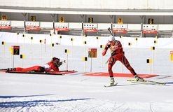 Biathlon in Holmenkollen, Oslo. Tora Berger from Norway in front, Darya Domracheva from Belarus still shooting in womens mass-start in w-cup in Holmenkollen Royalty Free Stock Image