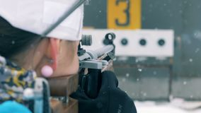 Biathlon shooting session of a sportswoman in a snowfall. 4K stock video footage