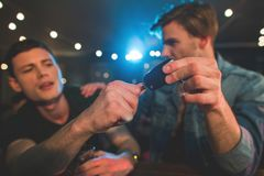 Bibacious man som ger strömbrytaretangent till kamraten Royaltyfri Fotografi