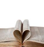 Bibbia aperta con lo spazio di forma e della copia del cuore immagini stock
