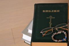 Bibbia chiusa con i vetri e un rosario russo Fotografia Stock