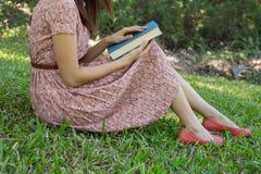 Bibbia della lettura della giovane donna in parco naturale Fotografia Stock