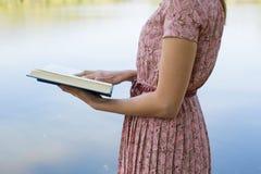 Bibbia della lettura della giovane donna in parco naturale Immagine Stock Libera da Diritti