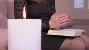 Bibbia della lettura della donna e pregare vicino alla candela bruciante archivi video