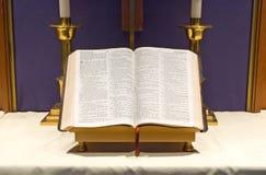Bibbia e candele sull'altare Immagine Stock