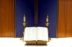 Bibbia e candele sull'altare Fotografia Stock