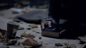 Bibbia misera della tenuta del vagabondo e pregare a Dio, forte credenza, fede fotografia stock libera da diritti