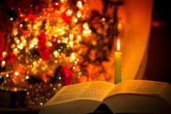 Bibbia santa con la candela su bokeh Fotografia Stock Libera da Diritti