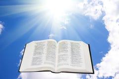 Bibbia santa nel cielo illuminato da una luce solare Immagini Stock Libere da Diritti